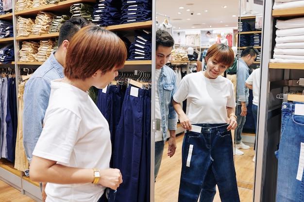 Aziatische vrouw die jeans in winkel kiezen