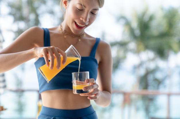 Aziatische vrouw die jus d'orange giet in de achtergrond van glas, zwembad en tuin.