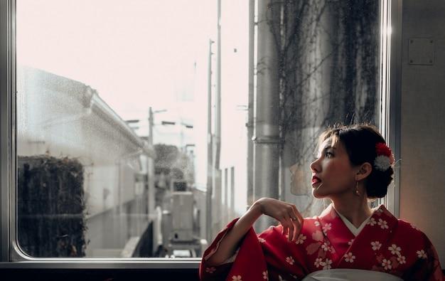 Aziatische vrouw die kimono draagt die door de klassieke de treinzitting van japan dichtbij het venster reist