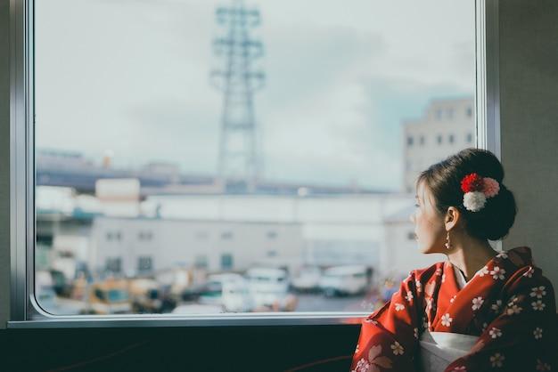 Aziatische vrouw die kimono draagt die door de klassieke de treinzitting van japan reist dichtbij het venster