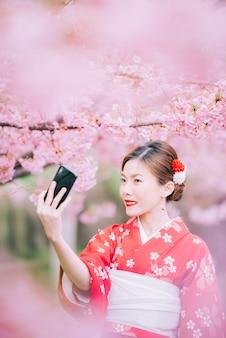 Aziatische vrouw die kimono draagt die smartphone met kersenbloesems, sakura in japan gebruikt.