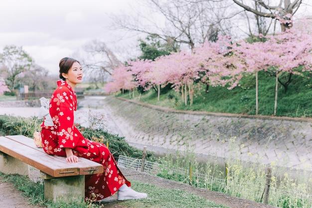 Aziatische vrouw die kimono met kersenbloesems draagt, sakura in japan.