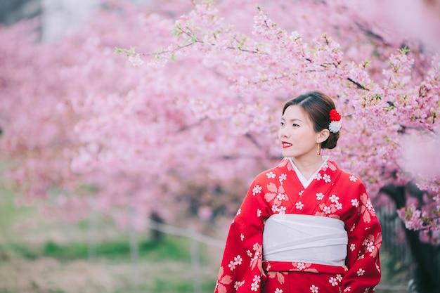 Aziatische vrouw die kimono met kersenbloesems draagt