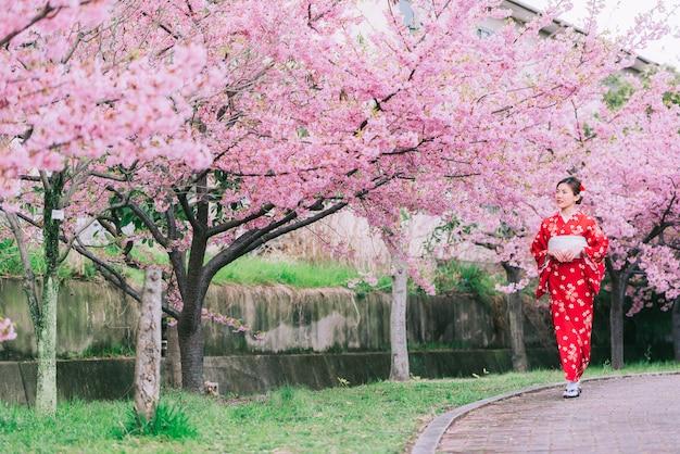 Aziatische vrouw die kimono met kersenbloesems, sakura in japan draagt.