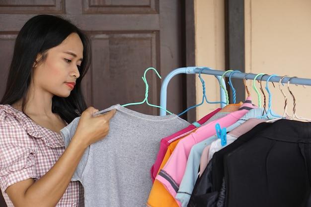 Aziatische vrouw die kleren aan het drogen is