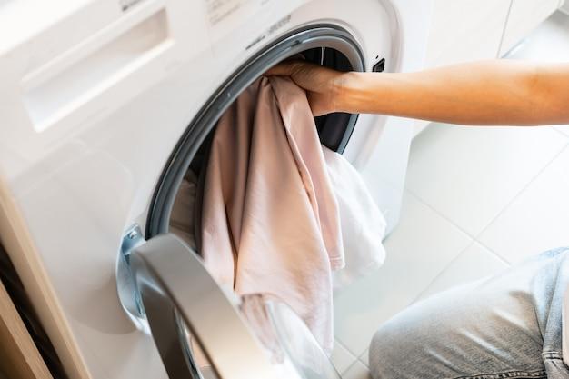 Aziatische vrouw die kleren thuis in de wasmachine in de keuken stopt wasconcept. bovenaanzicht