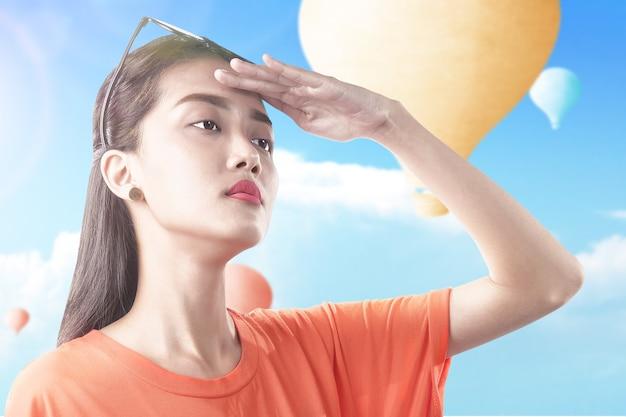 Aziatische vrouw die kleurrijke luchtballon bekijkt die met blauwe hemelachtergrond vliegt