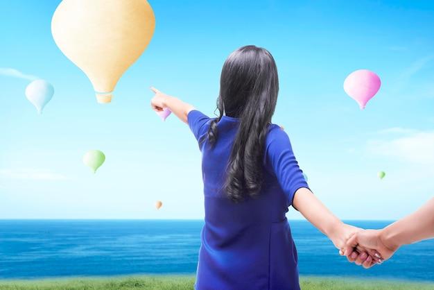 Aziatische vrouw die kleurrijke luchtballon richt die met blauwe hemelachtergrond vliegt