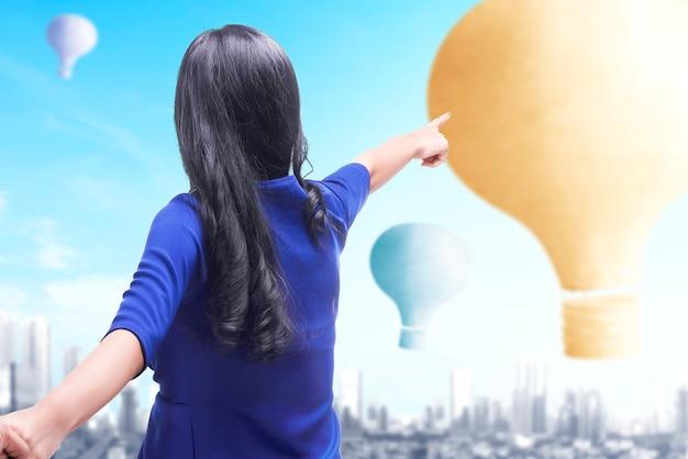 Aziatische vrouw die kleurrijke luchtballon richt die met stadsachtergrond vliegt