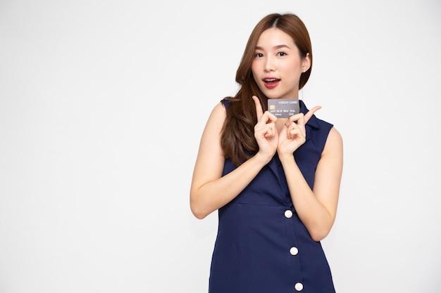 Aziatische vrouw die lacht, creditcard toont voor het maken van betaling of het betalen van online zaken.