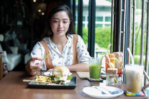 Aziatische vrouw die lacht hamburger eten bij café
