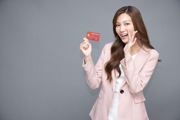Aziatische vrouw die lacht met creditcard geïsoleerd op een grijze achtergrond