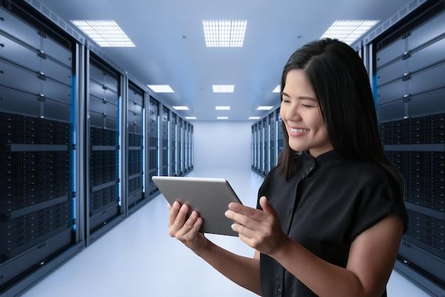 Aziatische vrouw die lacht met digitale tablet in serverruimte