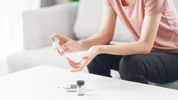 Aziatische vrouw die lancet op vinger gebruikt voor het controleren van de bloedsuikerspiegel door glucosemeter, gezondheidszorg en medisch, diabetes, glycemieconcept