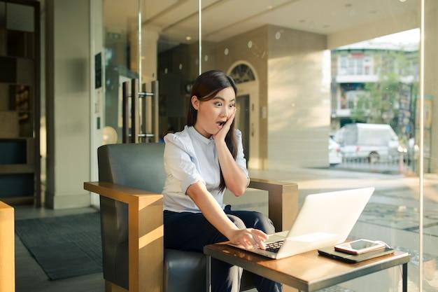 Aziatische vrouw die laptop met behulp van en zij heeft in koffie verrast