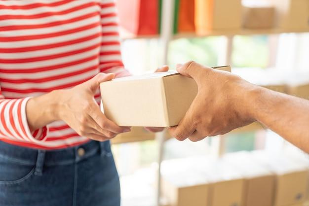 Aziatische vrouw die leveringspakket ontvangt - selectief aandachtspunt