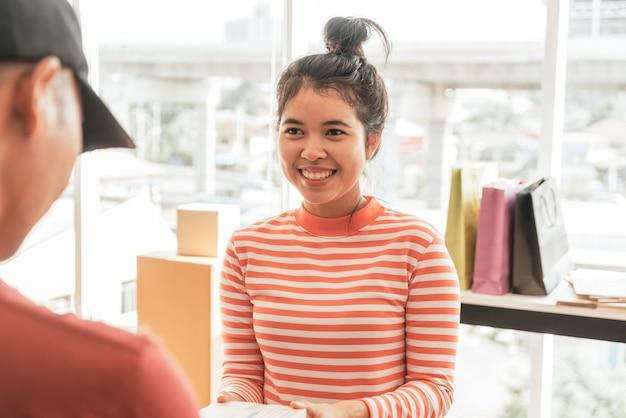 Aziatische vrouw die leveringspakket ontvangt