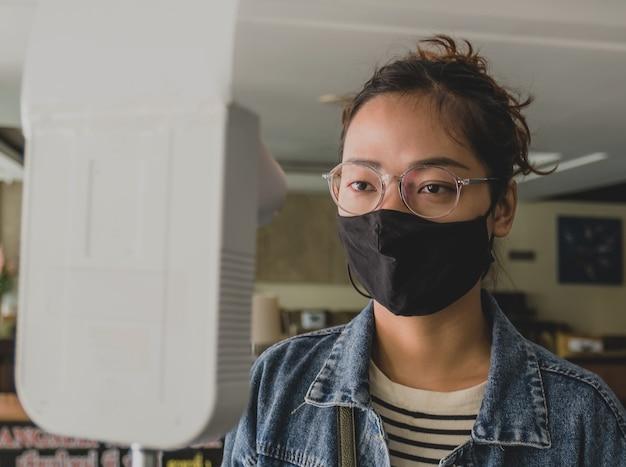 Aziatische vrouw die lichaamstemperatuur controleert met een temperatuurscannerdetector. Premium Foto