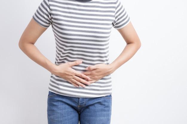 Aziatische vrouw die maagpijn op witte achtergrond heeft