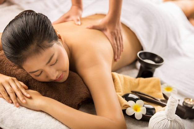 Aziatische vrouw die massage en kuuroordsalon heeft het concept van de schoonheidsbehandeling. ze is erg gelukkig