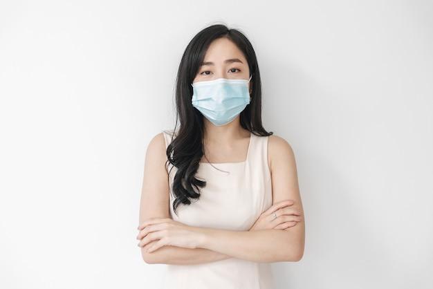Aziatische vrouw die medisch gezichtsmasker op wit draagt