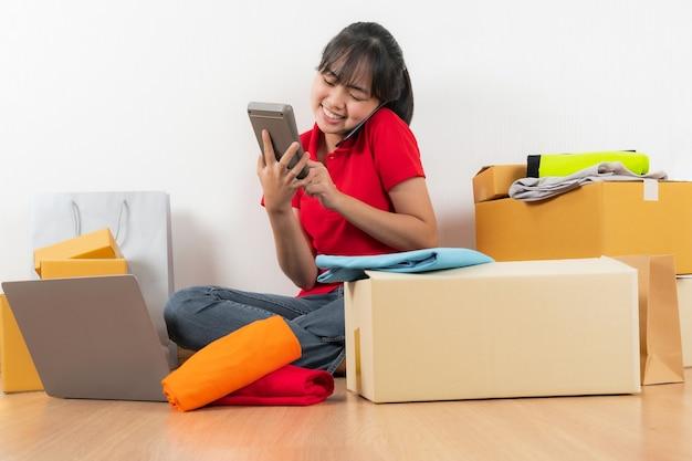 Aziatische vrouw die met calculator werkt, online ideeënconcept, online verkoper bedrijfswinkel thuis verkoopt
