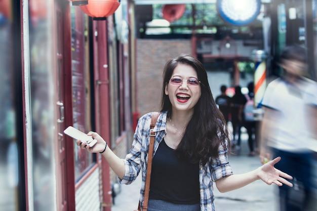 Aziatische vrouw die met gelukemotie lachen in modern winkelgebied
