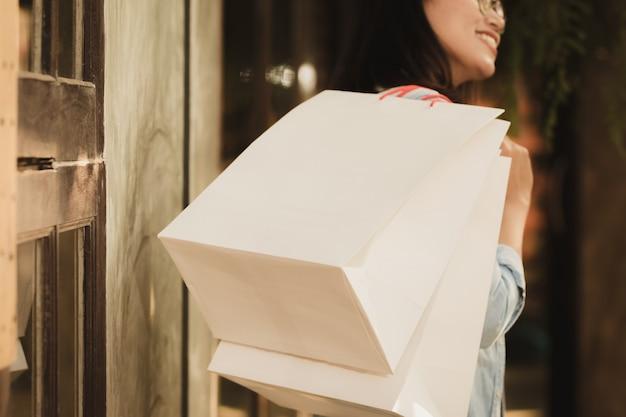Aziatische vrouw die met gelukkig in vrije tijd winkelt.
