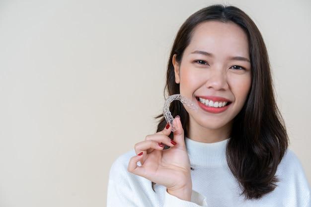 Aziatische vrouw die met hand glimlacht die tand aligner pal houdt