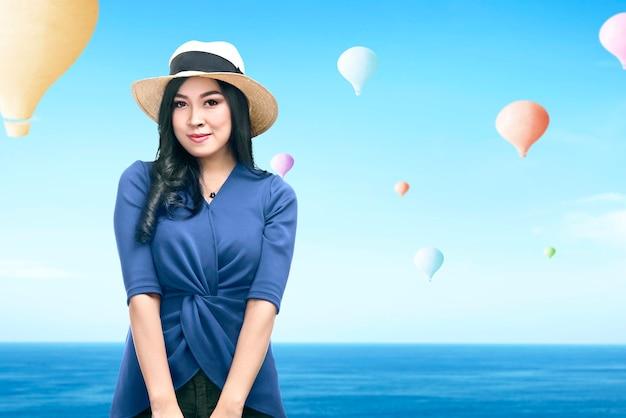 Aziatische vrouw die met hoed kleurrijke luchtballon bekijkt die met blauwe hemelachtergrond vliegt
