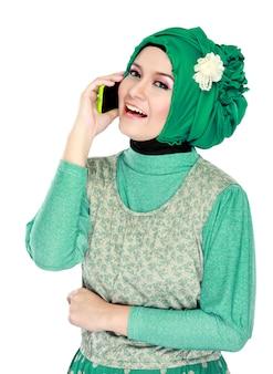 Aziatische vrouw die met hoofdsjaal door mobiele telefoon roept