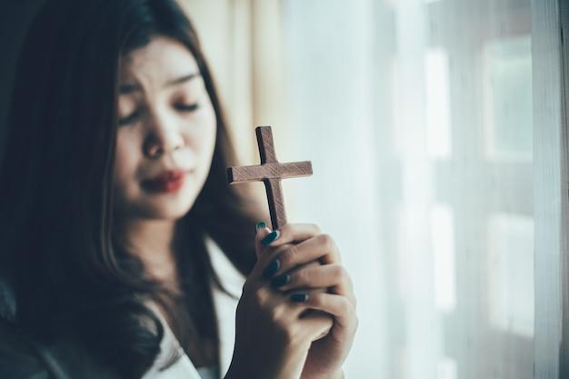 Aziatische vrouw die met houten kruis bidt en in god gelooft.