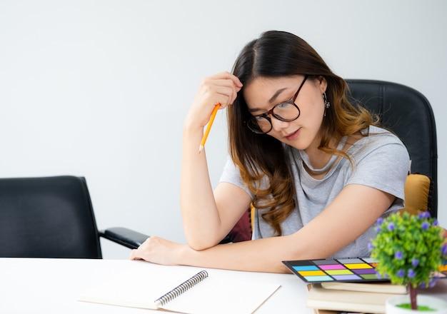 Aziatische vrouw die met lang gouden haar glazen draagt die bij het bureau zitten