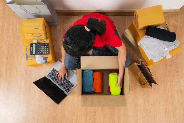 Aziatische vrouw die met laptop werkt, die online ideeënconcept verkoopt