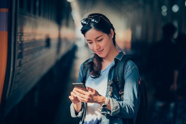 Aziatische vrouw die met mobiele telefoon reist