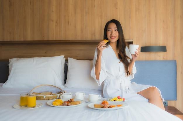 Aziatische vrouw die met ontbijt op bed geniet van