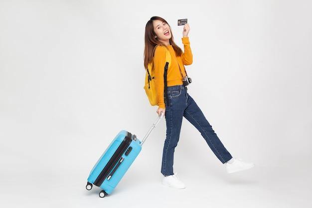 Aziatische vrouw die met reistas loopt en creditcard houdt die op witte achtergrond wordt geïsoleerd