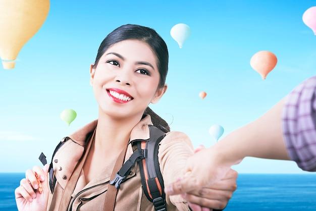Aziatische vrouw die met rugzak kleurrijke luchtballon bekijkt die met blauwe hemelachtergrond vliegt