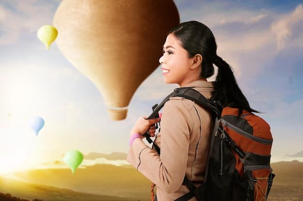 Aziatische vrouw die met rugzak kleurrijke luchtballon bekijkt die met dramatische hemelachtergrond vliegt