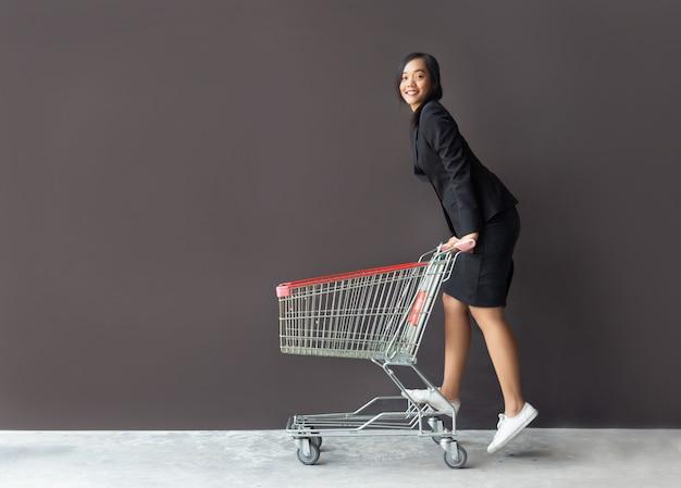 Aziatische vrouw die met troleykar winkelt
