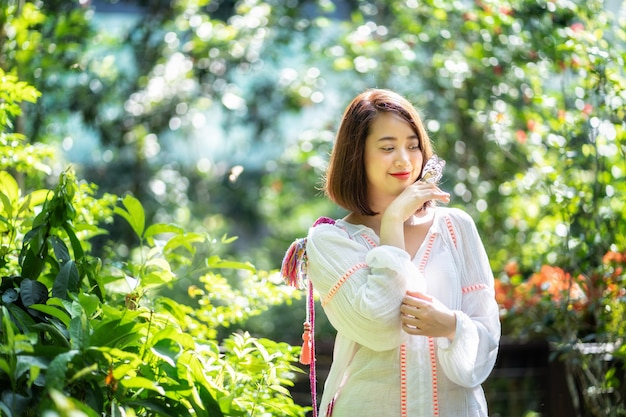 Aziatische vrouw die met vlinder op haar hand glimlacht.