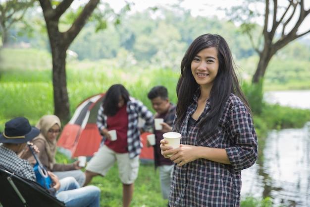 Aziatische vrouw die met vriend kampeert