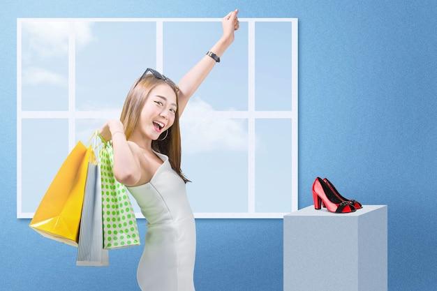 Aziatische vrouw die met zonnebril het winkelen zakken draagt die zich met blauwe muur bevinden