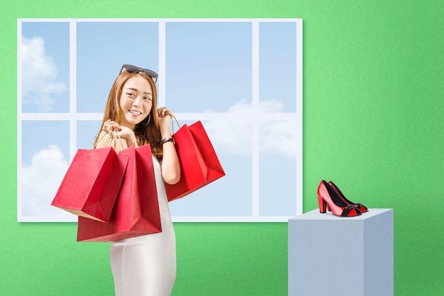 Aziatische vrouw die met zonnebril het winkelen zakken draagt die zich met groene muur bevinden