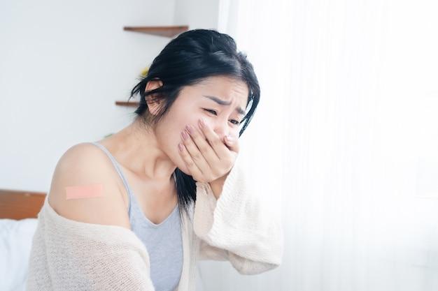 Aziatische vrouw die misselijkheid en braken voelt na ontvangst van het vaccin voor covid19