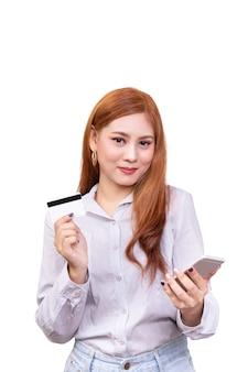 Aziatische vrouw die mobiele telefoon houdt en creditcard toont