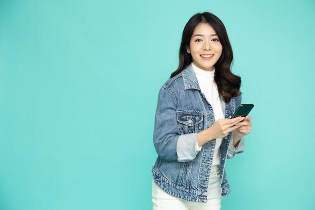 Aziatische vrouw die mobiele telefoon met behulp van en het jasje van jean draagt dat over groen wordt geïsoleerd.