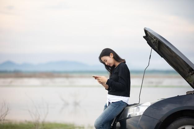 Aziatische vrouw die mobiele telefoon met behulp van terwijl het kijken en beklemtoonde mensenzitting na autoanalyse