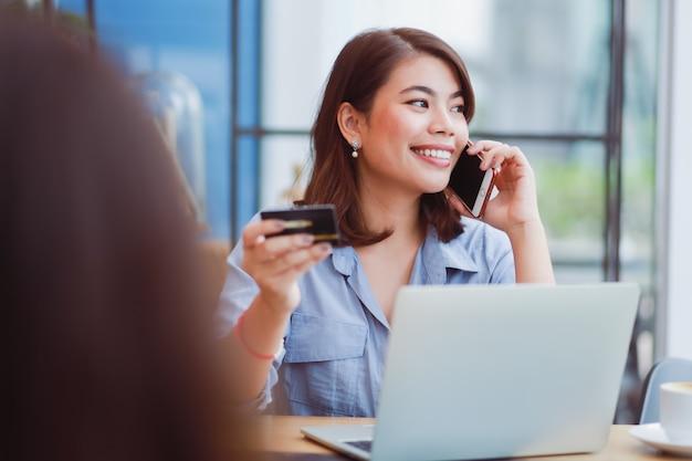 Aziatische vrouw die mobiele telefoon met creditcard en laptop computer voor het winkelen online betaling in koffiewinkel koffie met vrienden met behulp van