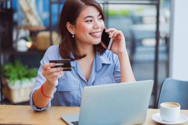 Aziatische vrouw die mobiele telefoon met creditcard en laptop computer voor het winkelen online betaling in koffiewinkel met behulp van